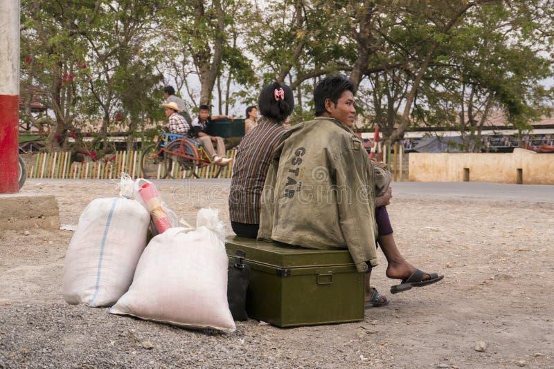 一对缅甸夫妇由路等待公共汽车 图库摄影