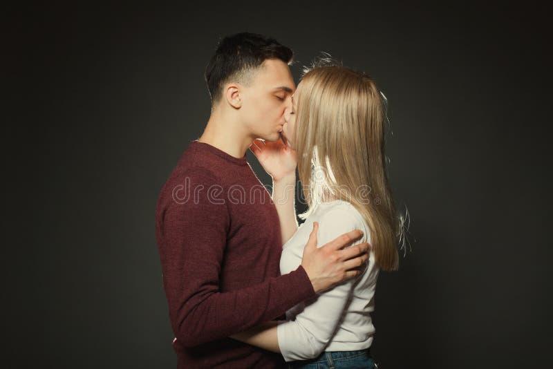 一对美好的年轻夫妇的画象在摆在黑暗的背景的演播室的爱的 亲吻的人和的女孩紧密  免版税库存照片