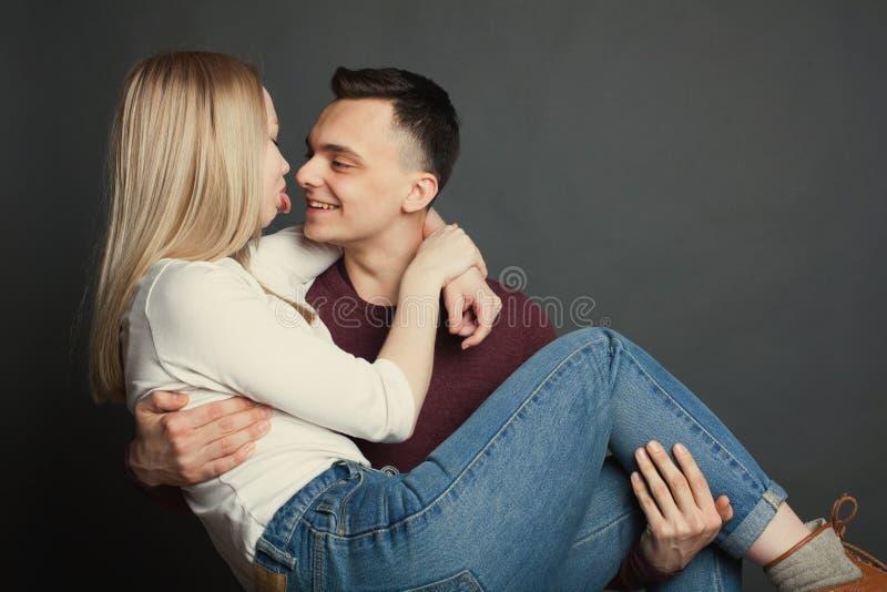一对美好的年轻夫妇的画象在摆在黑暗的背景的演播室的爱的 人对他的负心爱在他的胳膊和smil 免版税库存照片