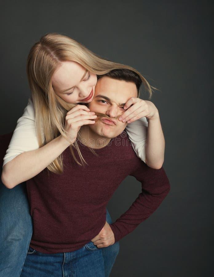 一对美好的年轻夫妇的画象在摆在黑暗的背景的演播室的爱的 做错误髭的愉快的夫妇由头发 免版税图库摄影