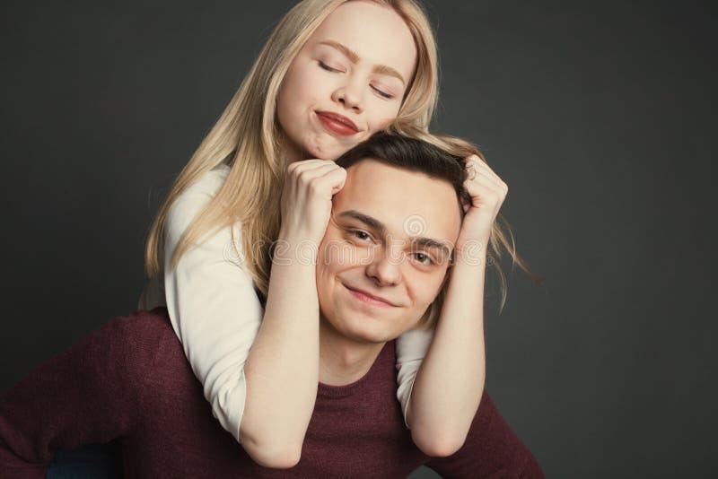 一对美好的年轻夫妇的画象在摆在黑暗的背景的演播室的爱的 女孩坐一个年轻人a的肩膀 库存照片