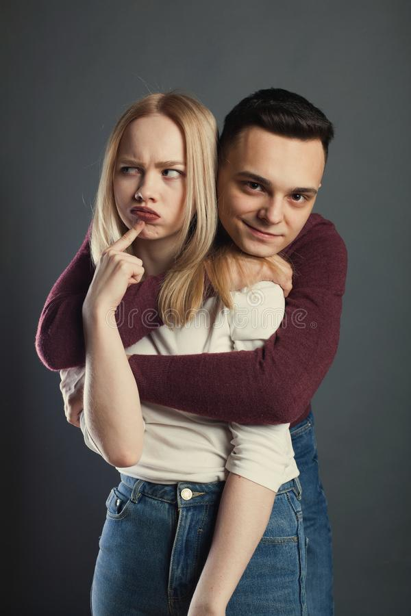 一对美好的年轻夫妇的画象在摆在黑暗的背景的演播室的爱的 图库摄影