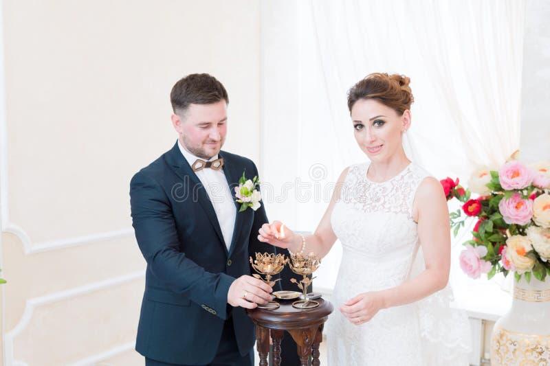一对美好的愉快的夫妇在注册处进行一种婚礼仪式与蜡烛照明设备 免版税库存图片