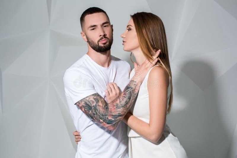 一对美好的年轻夫妇的画象在摆在白色背景的演播室的爱的 库存照片