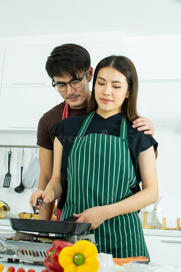 一对逗人喜爱的夫妇在厨房里烹调 库存图片