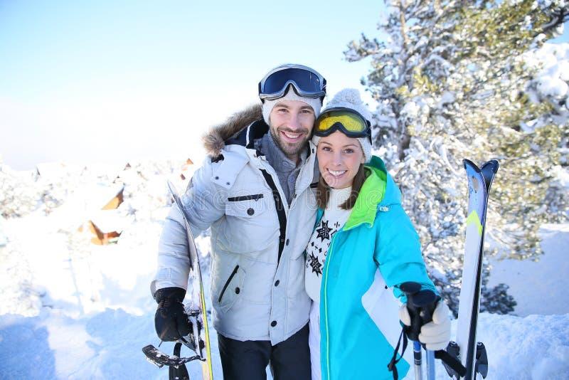 一对年轻夫妇的快乐的画象在滑雪的倾斜 免版税图库摄影