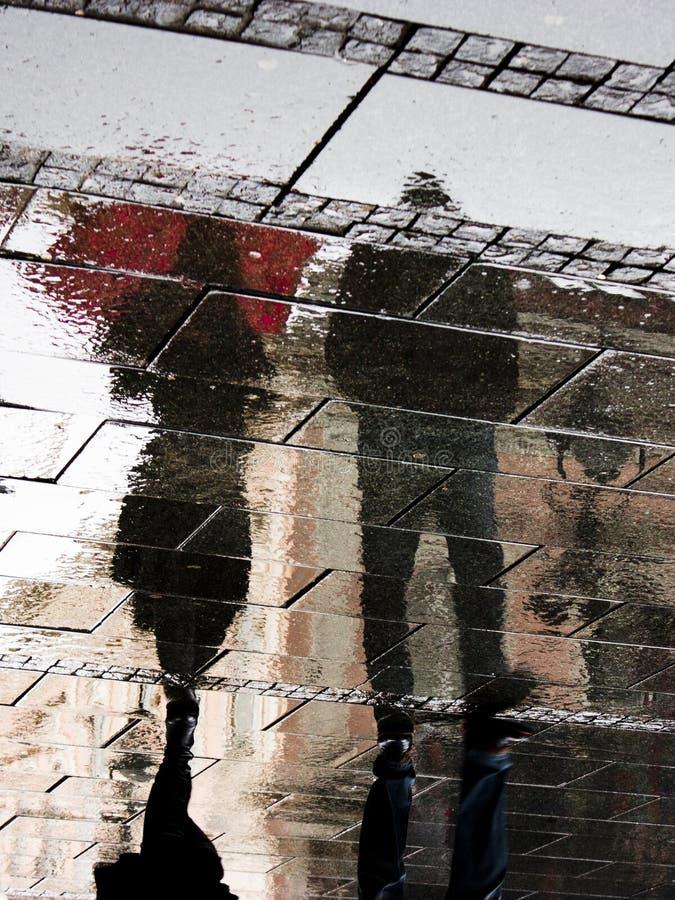 一对年轻夫妇的模糊的阴影和剪影在春雨下的 库存照片