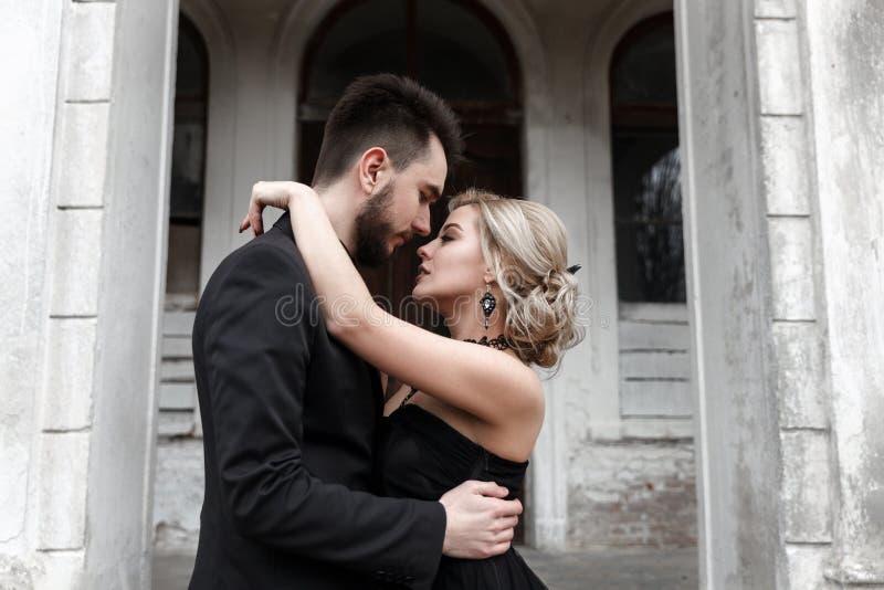 一对年轻夫妇的画象在黑衣服和礼服的 婚姻 库存照片