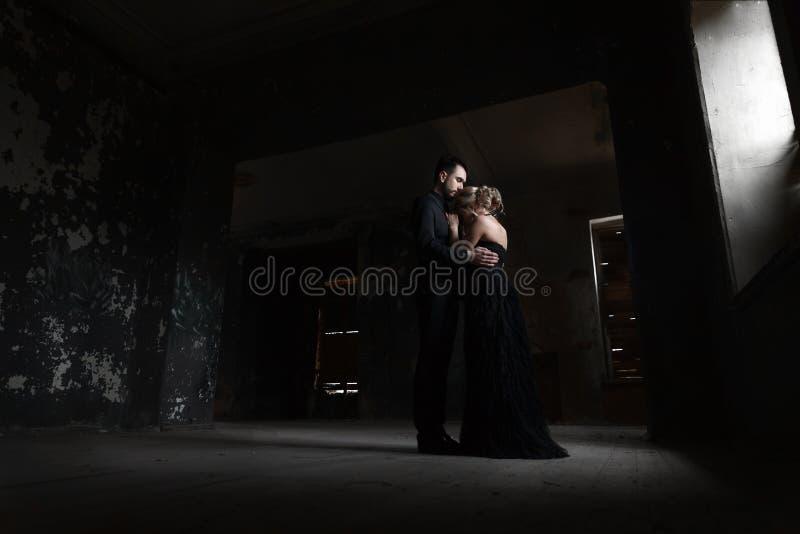 一对年轻夫妇的画象在黑衣服和礼服的 婚姻 免版税库存图片