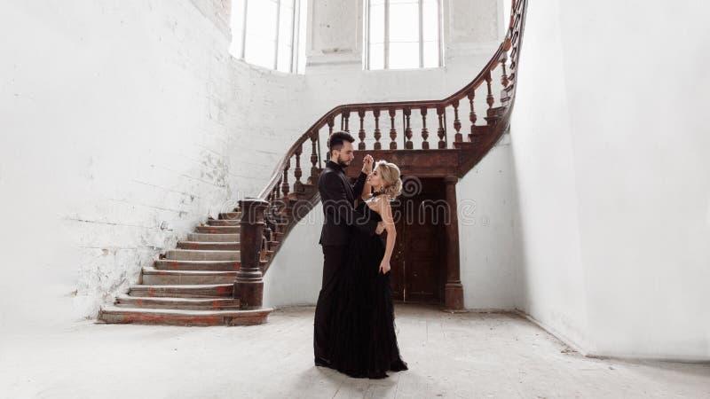 一对年轻夫妇的画象在黑衣服和礼服的 婚姻 免版税库存照片
