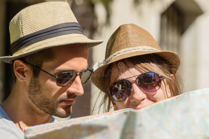 一对年轻夫妇,看地图 免版税图库摄影