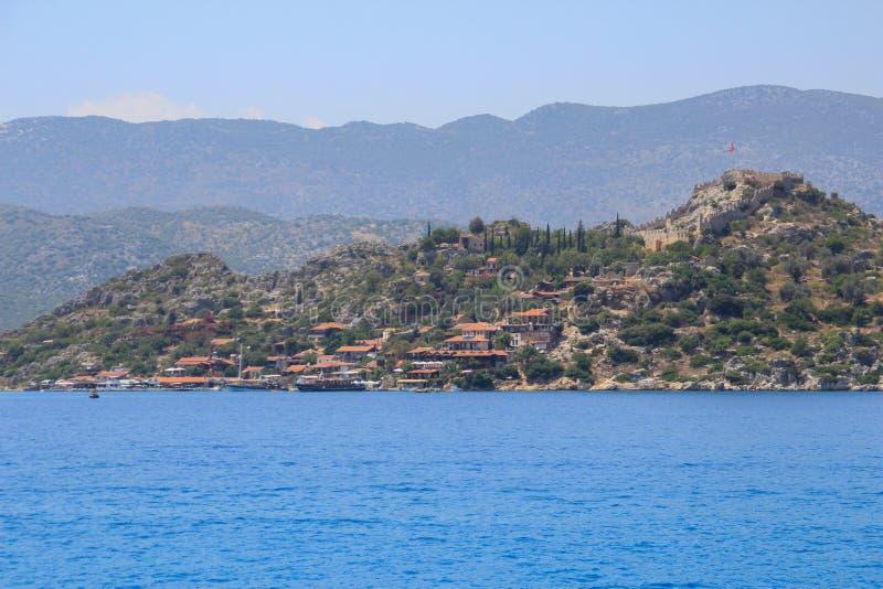 一小海滨城镇在博德鲁姆地区,土耳其在以岩石和山为背景的地中海 免版税库存照片