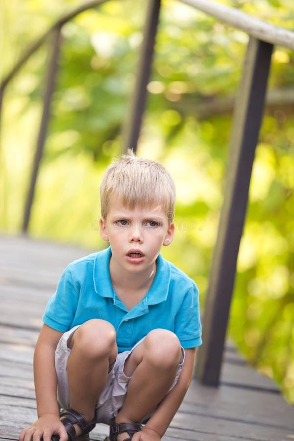 一小男孩下跪室外与一个严肃的表情 免版税库存照片