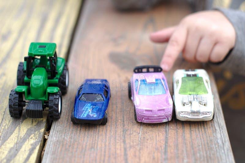 一小children& x27;s对一辆玩具汽车的手点在一许多在一张木红黄色桌上的汽车中 免版税库存图片