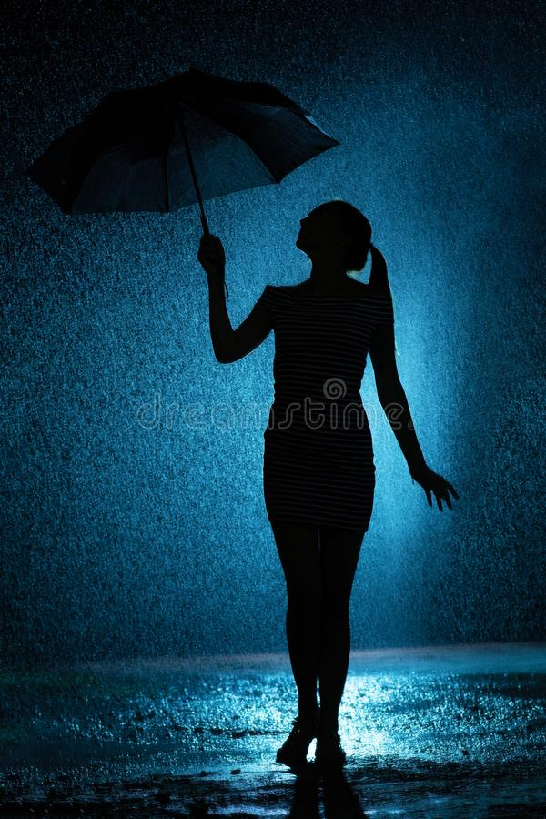 一少女的图的剪影有一把伞的在雨中,年轻女人是愉快的对水,概念天气滴  免版税库存照片