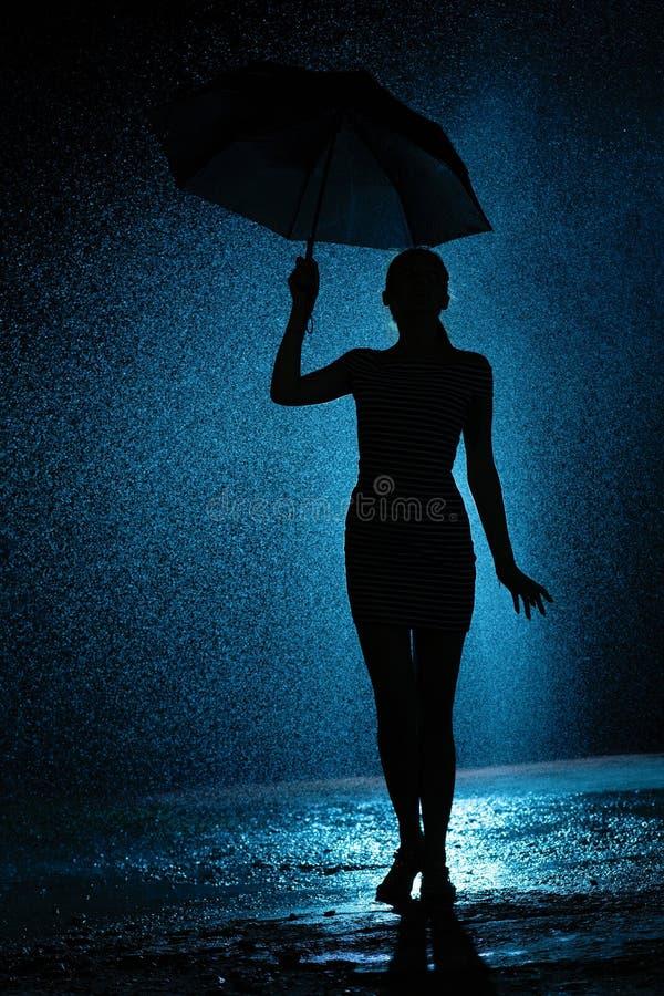 一少女的图的剪影有一把伞的在雨中,年轻女人是愉快的对水,概念天气滴  库存图片
