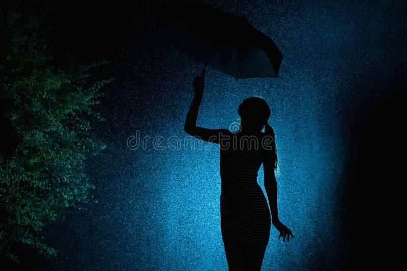 一少女的图的剪影有一把伞的在雨中,有亲手选的头发的一年轻女人是愉快的对下落  免版税库存图片