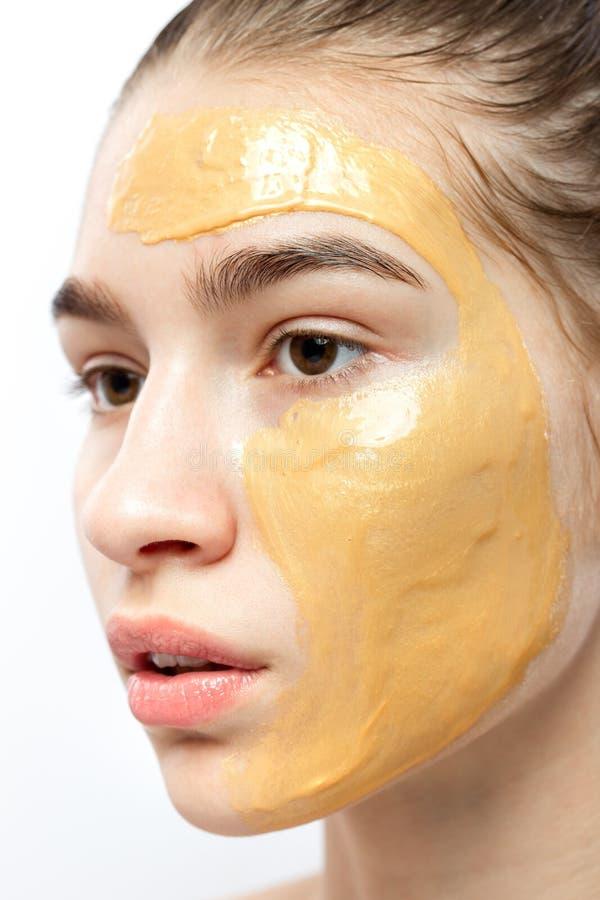 一少女的面孔有黄色化妆面具的对此 免版税库存照片