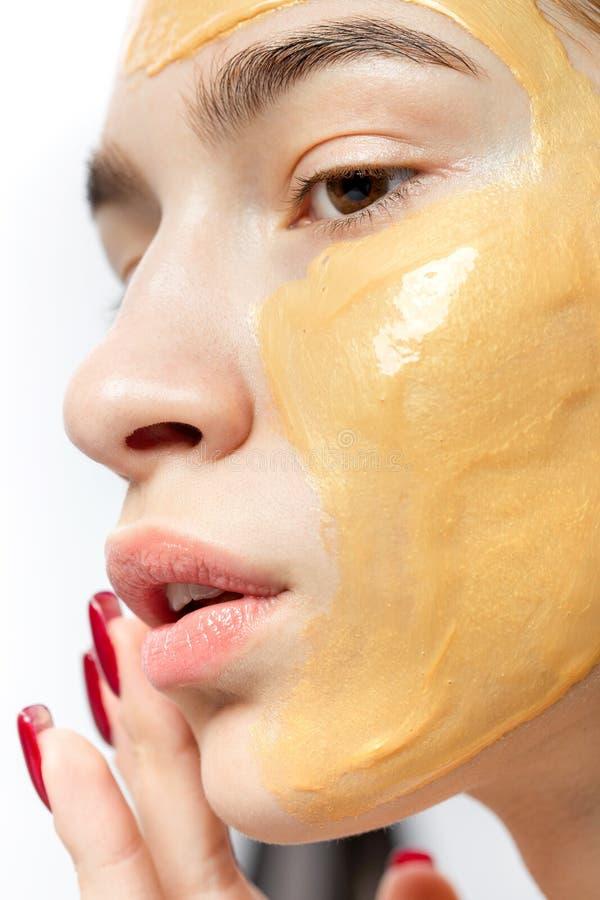 一少女的面孔有黄色化妆面具的对此 免版税图库摄影