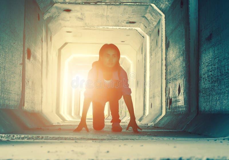 一少年沮丧的坐的背后照明在一个肮脏的隧道里面 库存照片