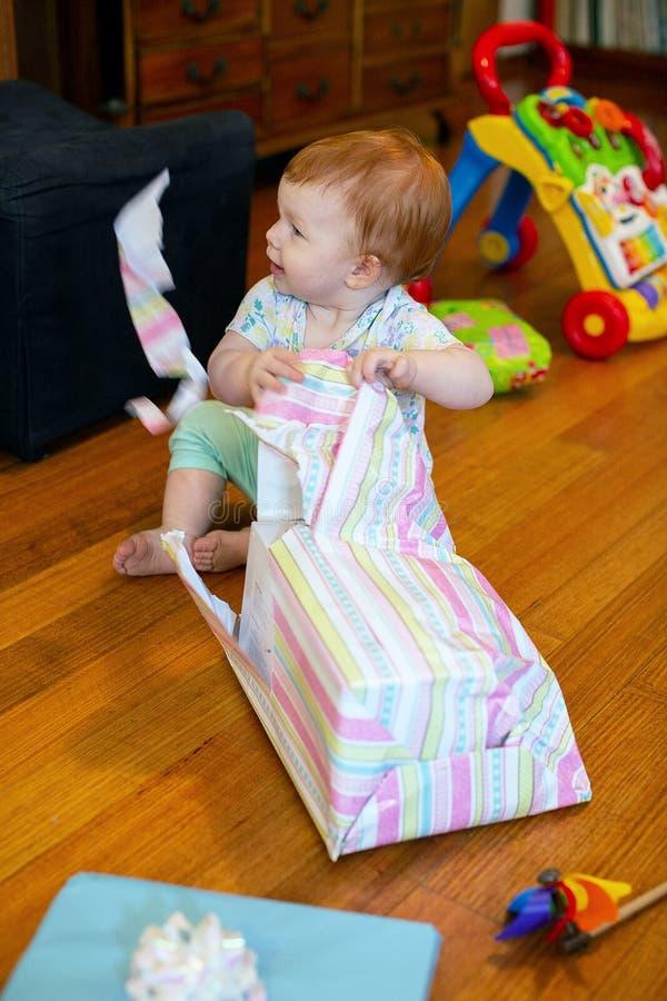 一岁生日那个带生日礼物的女孩 免版税图库摄影