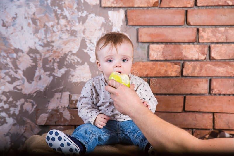 一岁的孩子坐桶以一红砖墙壁和пoing为背景截去举行的一个绿色苹果 免版税库存照片