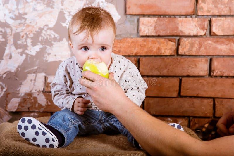 一岁的孩子坐桶以红砖墙壁为背景并且咬住了由他的父亲举行的一个绿色苹果 图库摄影