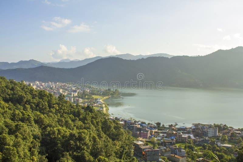 一巨大的山谷的看法有一个大城市的由绿色树木繁茂的山背景的湖  图库摄影