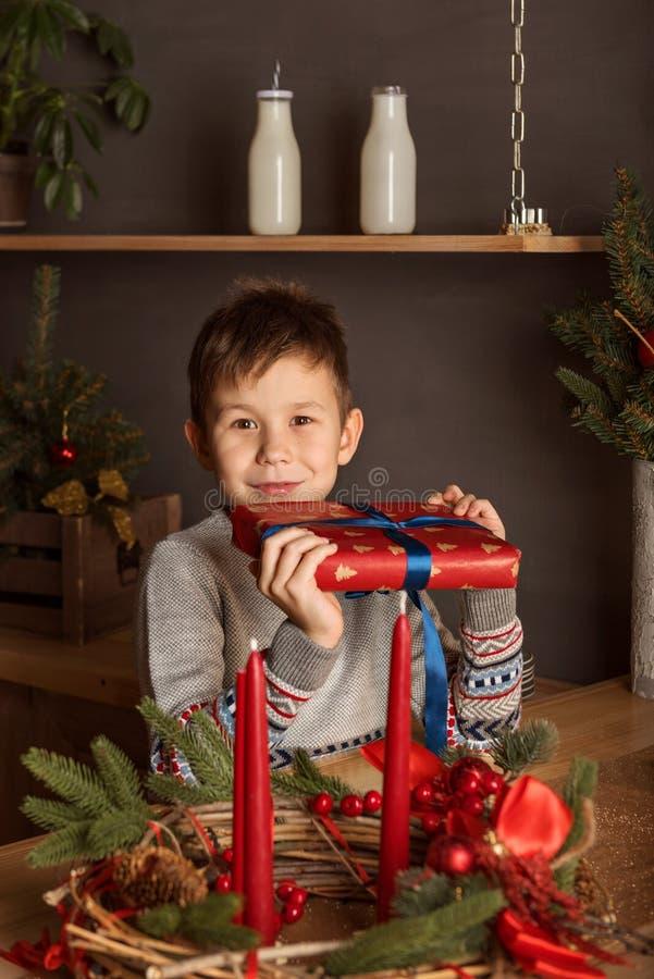 一帅哥的画象一件毛线衣的在有蜡烛的新年装饰的圣诞节厨房里 免版税图库摄影