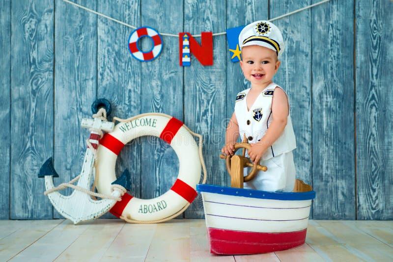 一年的男孩的Photoshoot 小船长,玩具船的水手有方向盘的 海锚和lifebuoy在灰色 库存照片