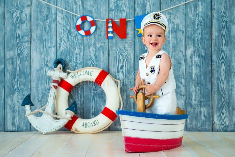一年的男孩的Photoshoot 小船长,玩具船的水手有方向盘的 海锚和lifebuoy在灰色 库存图片