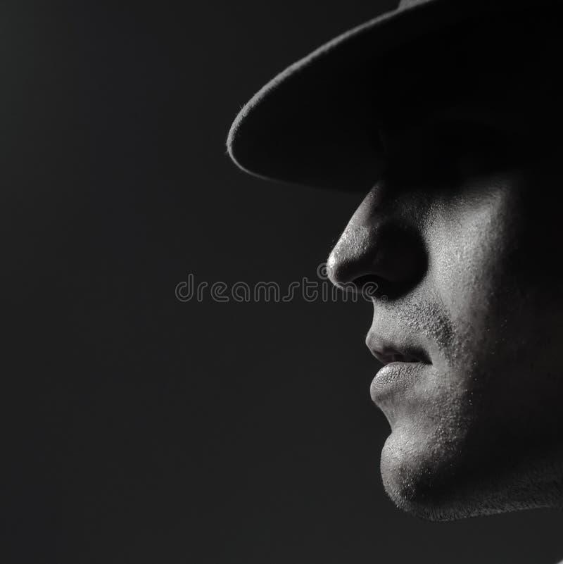 一年轻人的外形画象一个帽子身分的在深灰背景 关闭 经典样式 拷贝空间 在明亮的ligh 免版税库存图片