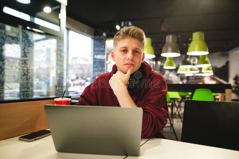 一年轻人的画象坐与在便当咖啡馆的一台膝上型计算机的便衣的,看照相机 免版税库存图片