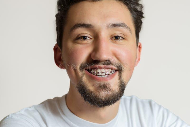 一年轻人的画象有括号微笑的 有括号的一愉快的年轻人在白色背景 免版税库存图片