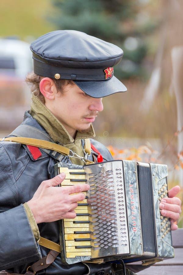 一年轻人的画象红军委员的军服的在与一个小风琴的内战期间在他的ha 免版税库存照片