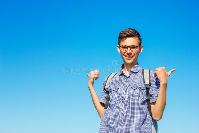 一年轻人的美丽的画象戴眼镜的在天空蔚蓝背景 免版税库存照片