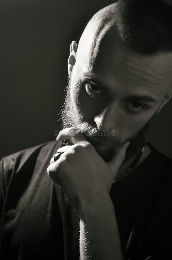 一年轻人的黑白画象有一个胡子的在灰色背景 图库摄影