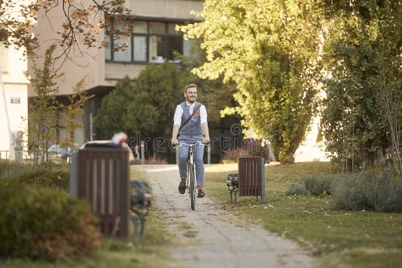 一年轻人,20-29岁,佩带的行家衣服,聪明偶然,微笑,享用骑在公园路足迹的自行车 免版税库存图片