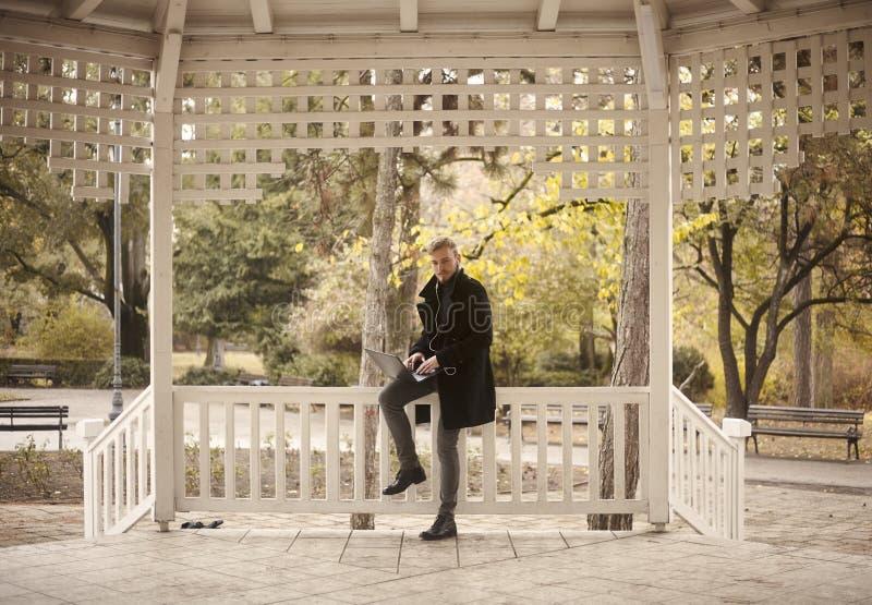 一年轻人,20-29岁,坐篱芭户外在公园,当使用他的膝上型计算机时 免版税库存照片