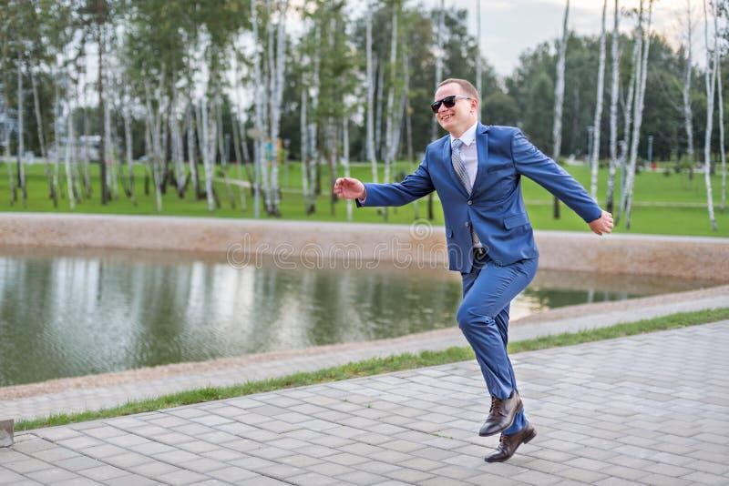 一年轻商人跑的跳跃在街道上 免版税库存图片