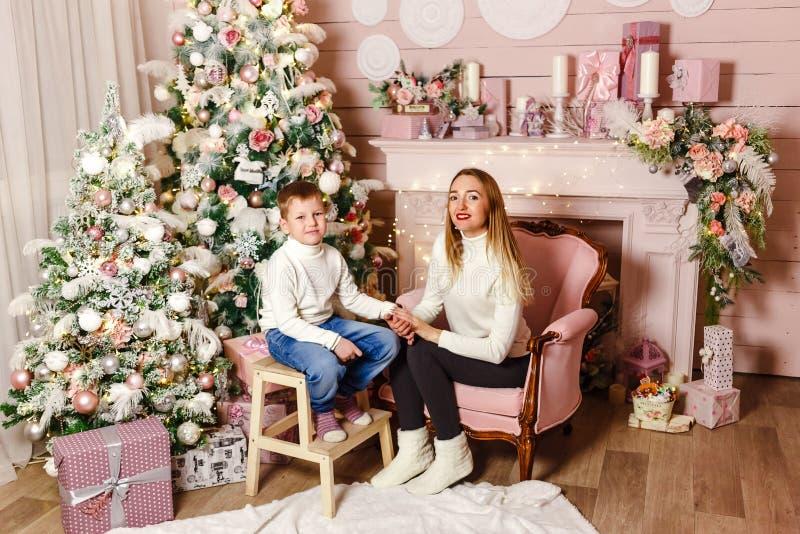 一年轻女人和一七岁的童颜在照相机在圣诞节设置 在圣诞节的系列 两个绿色牛仔裤妈妈儿子顶层佩带 库存图片