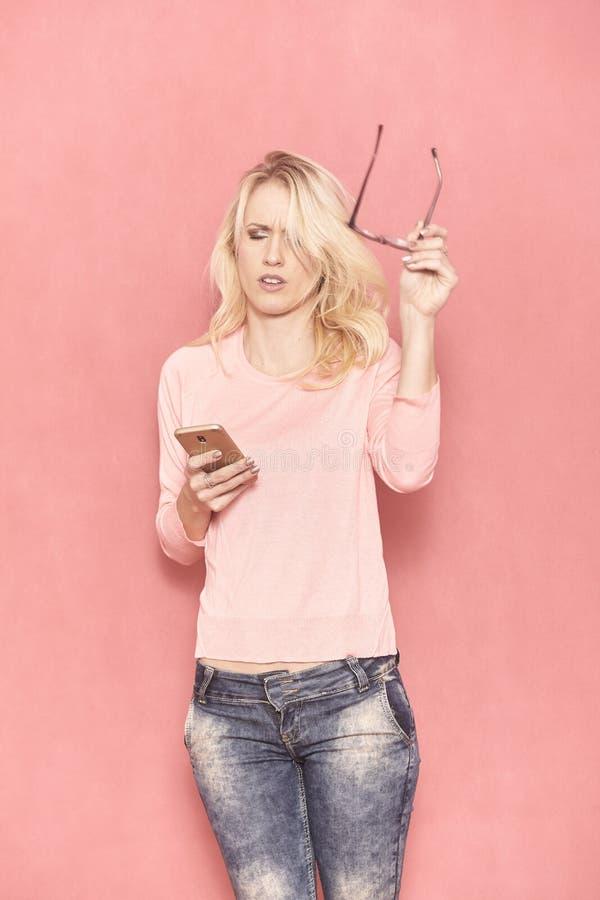 一年轻女人疲乏使用她的智能手机,20-29岁,长期金发 库存图片