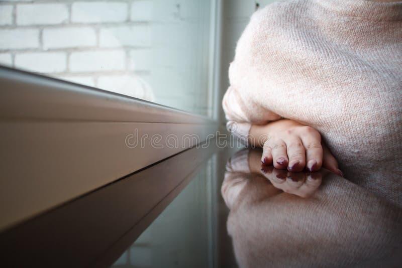 一年轻女人的手一件桃红色毛线衣的在棕色窗台在它上说谎和被反射 免版税库存照片