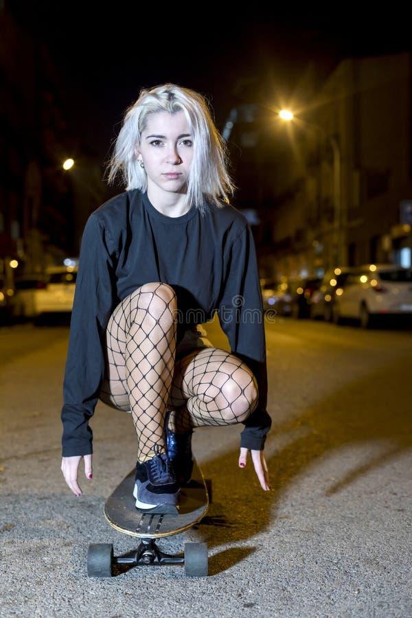 一年轻女人的正面图简而言之在一个长的委员会的,当注视着照相机夜在城市时 免版税库存照片