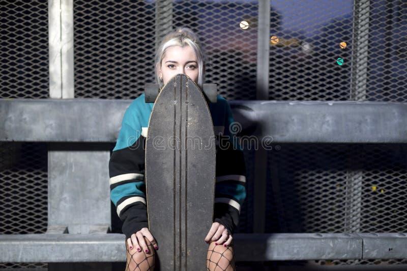 一年轻女人的正面图简而言之拿着一个长的委员会的,当坐篱芭在晚上时 库存图片