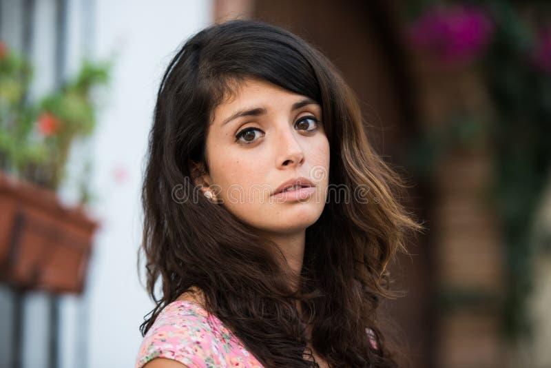 一年轻女人的画象在调查照相机的一个tipical西班牙庭院 免版税库存图片