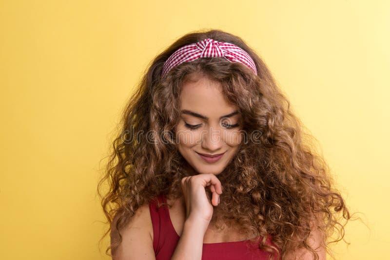 一年轻女人的画象有头饰带的在黄色背景的一个演播室 库存图片