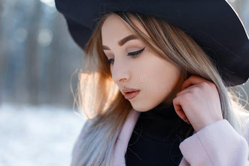 一年轻女人的画象有棕色眼睛的与有金发的嘴唇有在典雅的黑帽会议的美好的构成的 免版税图库摄影