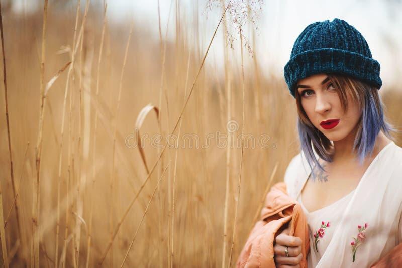 一年轻女人的画象被编织的帽子和白色礼服的,在金黄麦田的背景 免版税库存图片