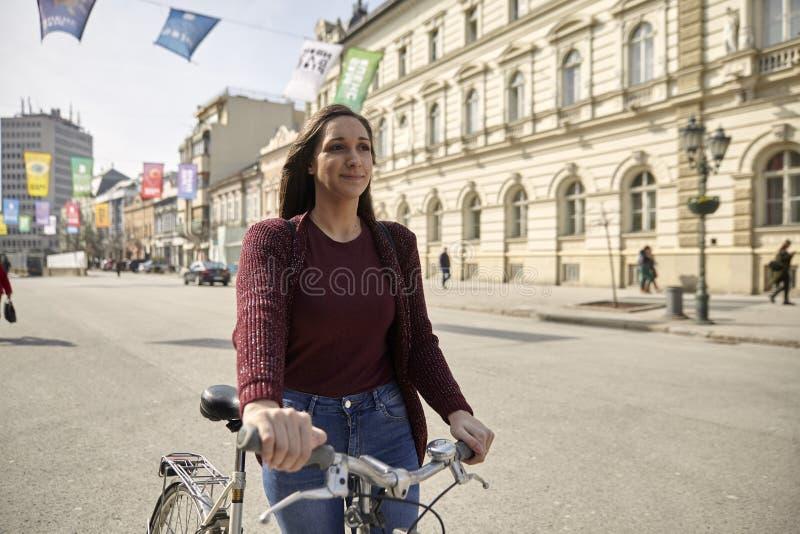 一年轻女人,今后看,推挤她的自行车在城市,步行区域欧洲老建筑学样式 库存图片